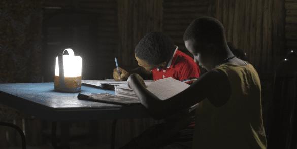 Deux écoliers font leurs devoirs avec la lanterne Total Access To Energy Solutions.