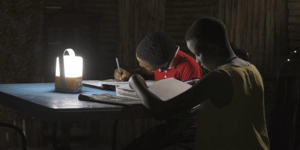 Two schoolchildren do their homework with the Total Access To Energy Solutions lantern.